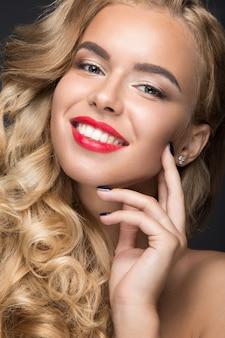 Bella donna bionda con riccioli, labbra rosse e un sorriso sul suo viso