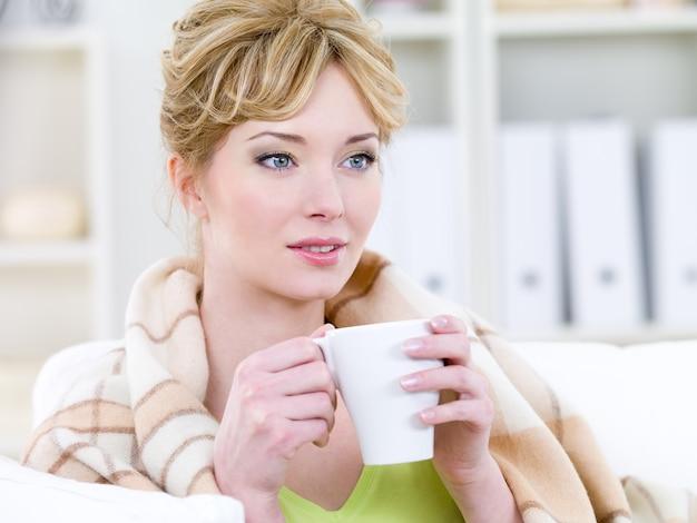 Bella donna bionda con un sorriso facile bere caffè caldo - al chiuso