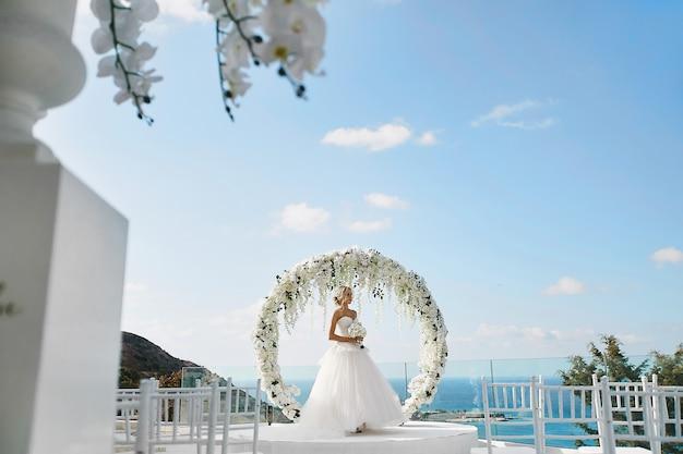 Bella donna bionda di modello nel vestito da sposa bianco con un mazzo di fiori in sue mani che stanno vicino intorno all'arco floreale rotondo di nozze all'aperto