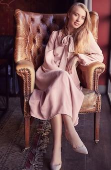 Bella donna bionda elegante in vestito rosa che si siede in poltrona di cuoio