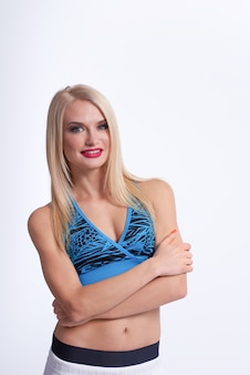Bella donna bionda fitness sorridente con le braccia incrociate in posa con fiducia