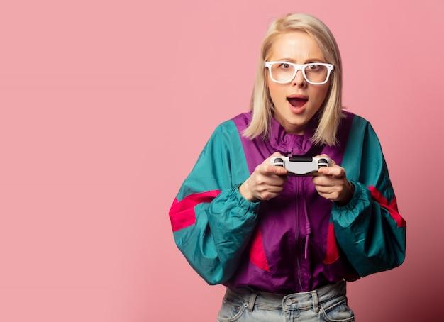 Bella donna bionda in abiti anni '90 con joystick