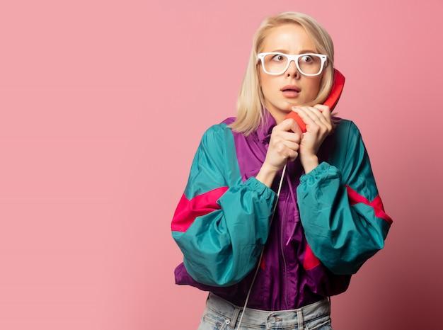 Bella donna bionda in abiti anni '90 con l'auricolare