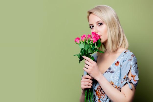 Bella donna bionda in abito con rose sul muro verde