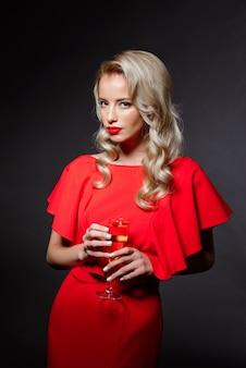 Bella donna bionda in abito da sera in posa, tenendo il bicchiere di champagne