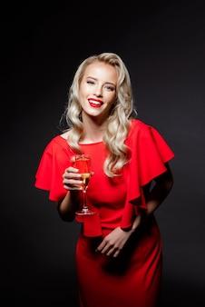 Bella donna bionda in abito da sera sorridente, tenendo il bicchiere di champagne