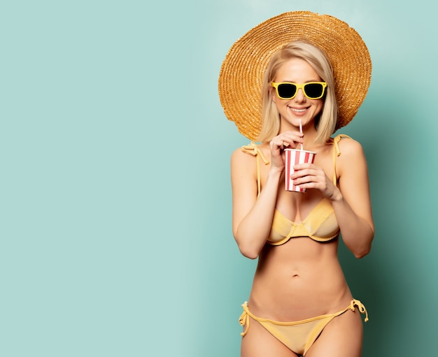 Bella donna bionda in bikini con un bicchiere di carta