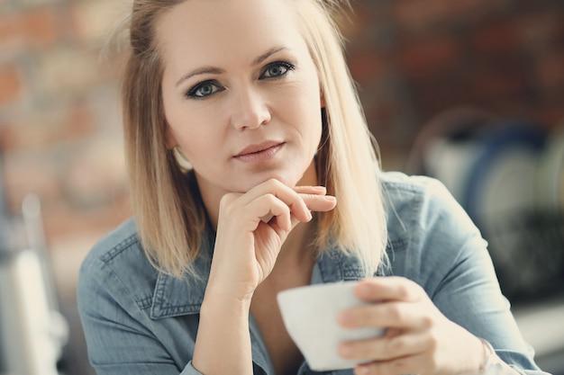 Bella donna bionda in posa con una tazza di caffè