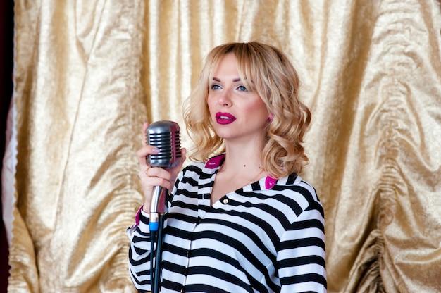 Bella donna, bionda, microfono. cantando, bel sorriso