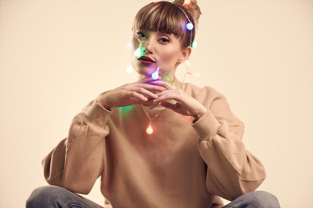 Bella donna bionda positiva con le luci di natale sulla testa