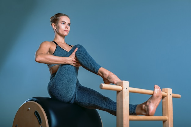 Bella donna bionda positiva viene preparata eseguendo esercizio di pilates, allenamento su attrezzature a botte. concetto di fitness, stile di vita sano, plastica. copia spazio, banner sportivo per la pubblicità.