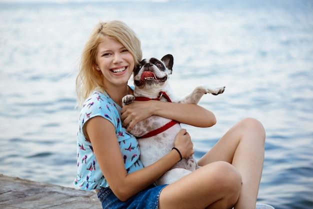 Bella donna bionda seduta, giocando con il bulldog francese vicino al mare