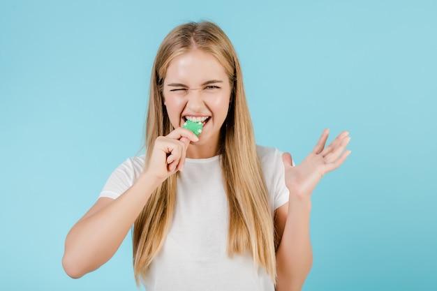 Bella donna bionda sorridente con il chip di poker dal casinò online isolato sopra il blu