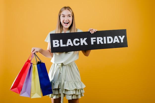 Bella donna bionda sorridente con il segno di venerdì nero e sacchetti della spesa variopinti isolati sopra giallo