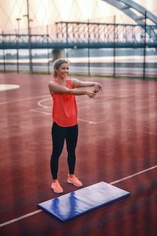 Bella donna bionda sorridente in abiti sportivi che stanno sulla corte e che allungano braccio