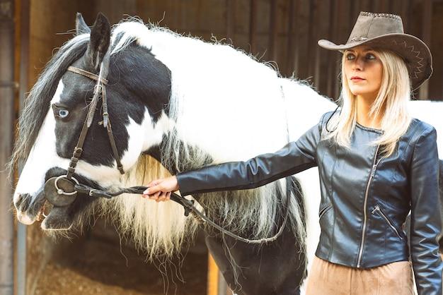 Bella donna bionda stile country con il cavallo in bianco e nero