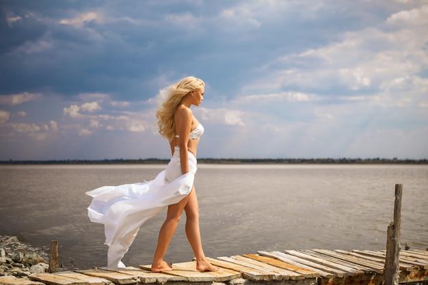 Bella donna bionda sulla spiaggia in un costume da bagno bianco