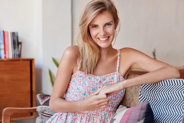 Bella donna bionda vestita con abiti alla moda, si siede su un comodo divano, ha un ampio sorriso, si sente rilassata a casa, passa il tempo contro gli interni domestici. persone, felicità, concetto di stile di vita
