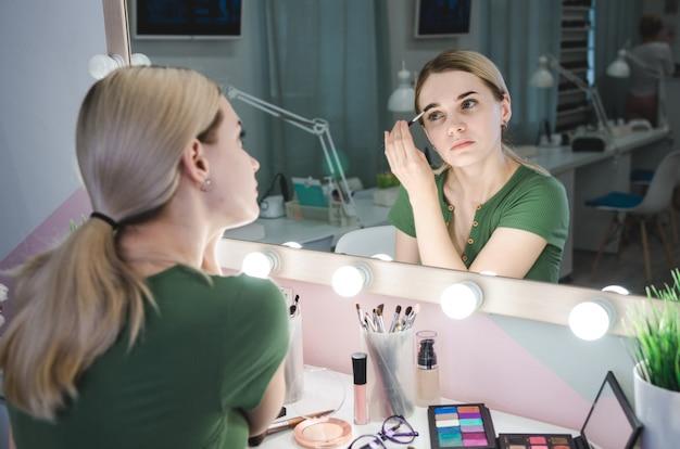 Bella donna bionda vicino allo specchio nella stanza di trucco