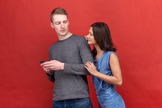 Bella donna bruna che brucia fissa incredulo spionaggio per telefonare al suo ragazzo.