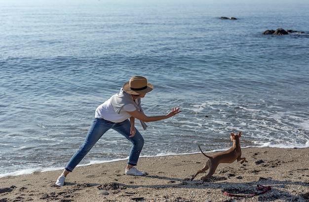 Bella donna bruna che gioca con il cane sulla spiaggia