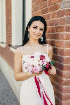 Bella donna bruna con aspetto affascinante, indossa orecchini, abito da sposa bianco e detiene un bellissimo bouquet
