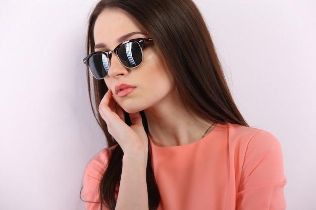 Bella donna bruna con occhiali da sole e capelli lunghi in posa