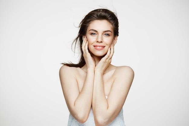 Bella donna bruna con pelle fresca sana e capelli volanti sorridenti toccando il viso.