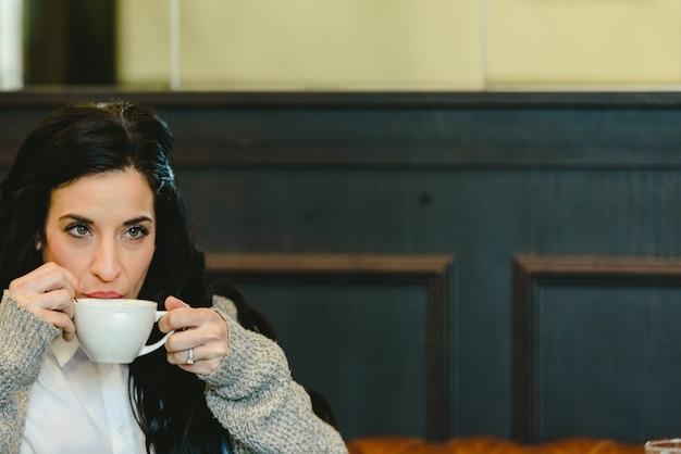 Bella donna bruna facendo colazione bere caffè in un ristorante europeo.