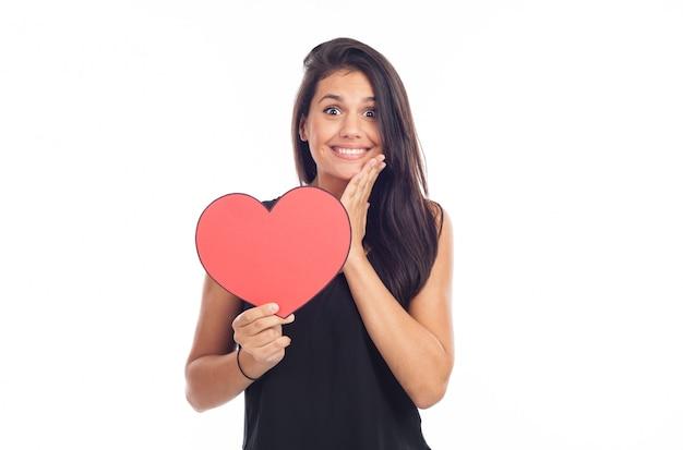 Bella donna bruna felice holding e mostrando un grande cuore rosso