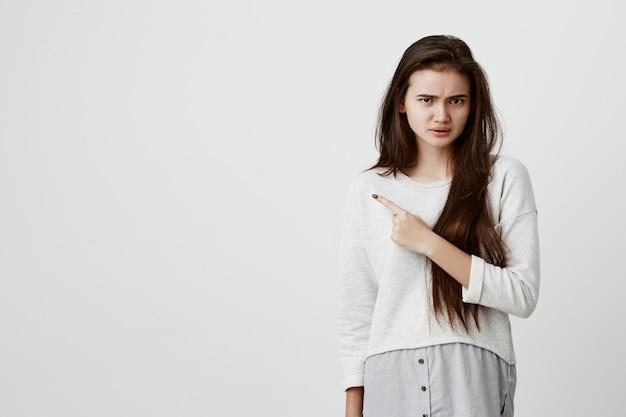 Bella donna bruna in abiti casual che puntava il dito indice contro il muro bianco grigio con sguardo insoddisfatto, accigliato, con espressione negativa del viso