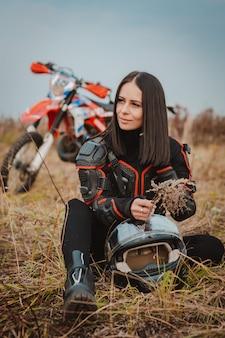 Bella donna bruna in abito da moto. pilota di motocross femminile accanto alla sua moto russia mosca 20 ottobre 2019