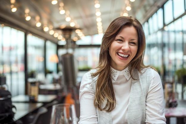 Bella donna bruna in caffè a parlare e sorridere.