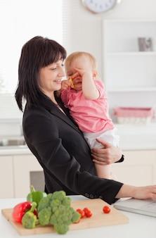 Bella donna bruna in tuta che tiene il suo bambino tra le braccia mentre si lavora con il suo computer portatile