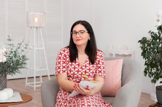 Bella donna bruna medico psicologo con gli occhiali seduto in un ufficio luminoso, sorridente e scrivendo sulla carta