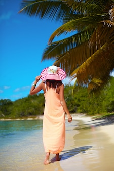 Bella donna calda in cappellino da sole variopinto e vestito che cammina vicino all'oceano della spiaggia il giorno di estate caldo vicino alla palma