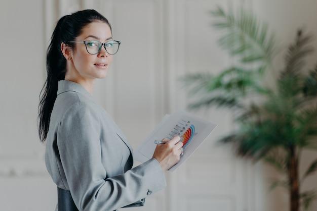 Bella donna castana che controlla i documenti
