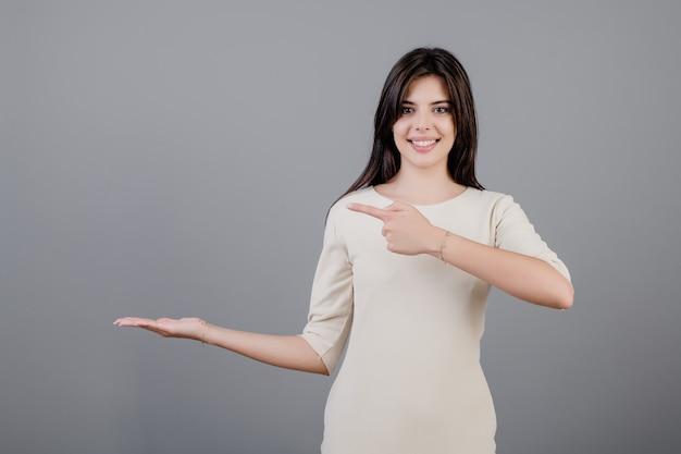 Bella donna castana che sorride felicemente e che indica dito al copyspace a disposizione isolato sopra grey