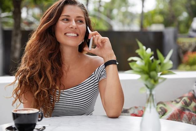 Bella donna castana con espressione felice e telefono nella caffetteria con terrazza all'aperto
