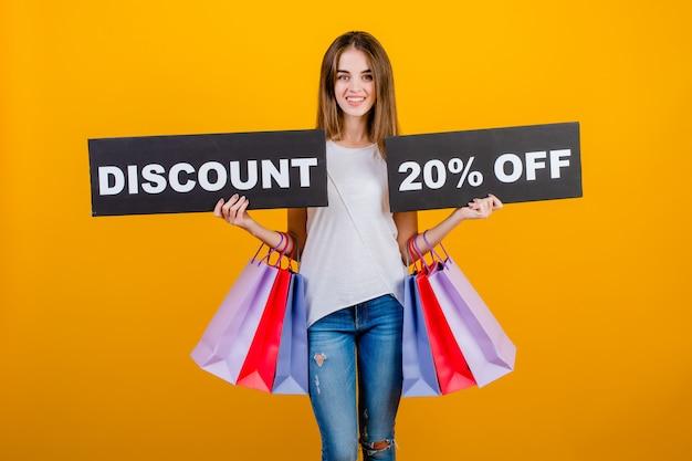 Bella donna castana con i sacchetti della spesa variopinti e il segno del 20% di sconto del testo del copyspace isolato sopra giallo