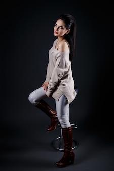 Bella donna castana in maglione beige che si siede su uno sgabello da bar