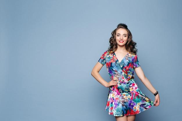 Bella donna castana in vestito floreale alla moda che tiene la sua gonna con il braccio.