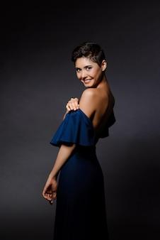 Bella donna castana nel sorridere del vestito da sera