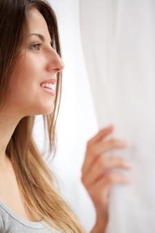 Bella donna caucasica che esamina finestra
