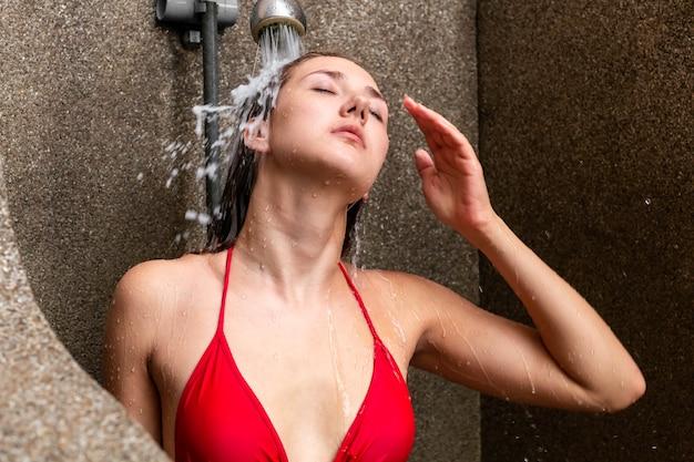 Bella donna caucasica in bikini rosso che fa la doccia fuori.