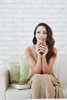 Bella donna caucasica seduto sul divano di casa, tenendo la tazza e guardando lontano