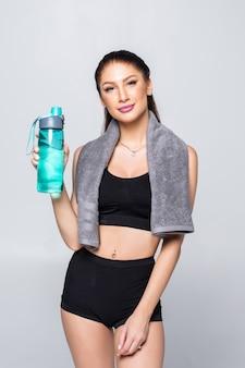 Bella donna caucasica sportiva che giudica un bicchiere d'acqua isolato