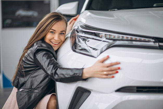 Bella donna che abbraccia un'auto