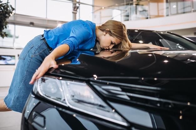 Bella donna che abbraccia un'automobile in uno showrrom dell'automobile