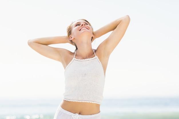 Bella donna che allunga le sue braccia sulla spiaggia